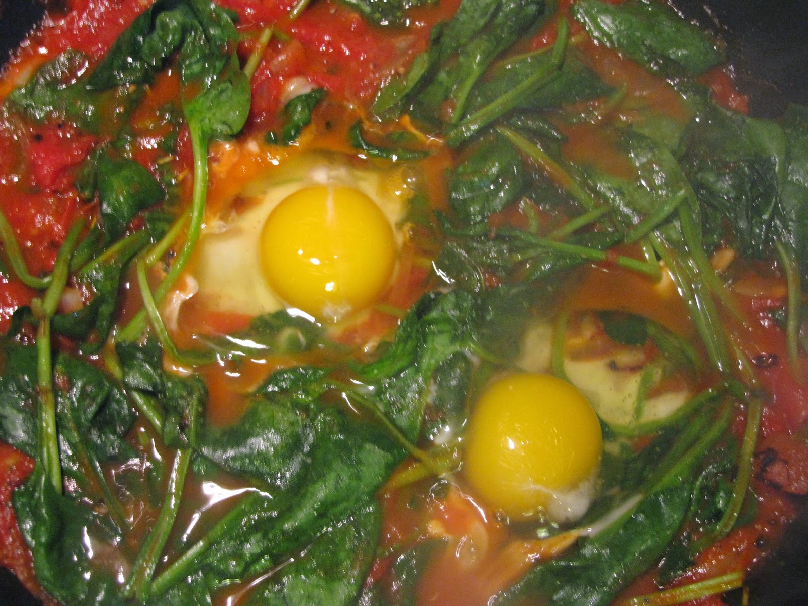 Eggs encased in surrounded by partly wilted spinach in tomato sauce