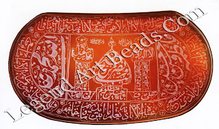 The cursive inscriptions of this amulet are broken up to make compartments, some arranged inside a dome and its flanking minarets, others around it and in the two parts of the central oval area and in the four compartments surrounding it.