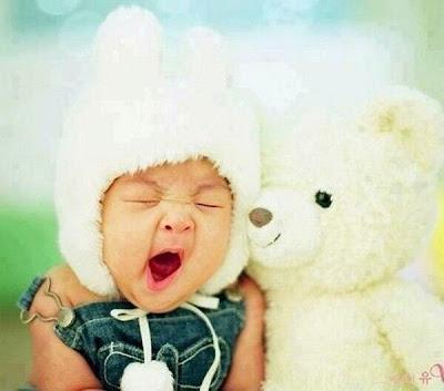 Gähnendes Baby und Teddy Bär
