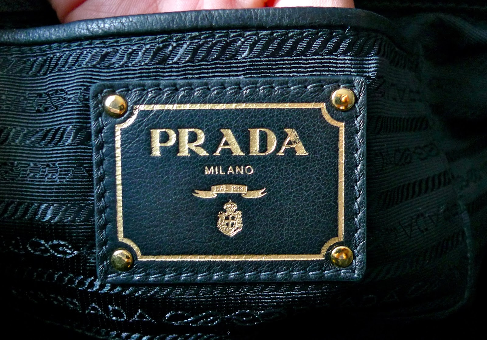 open pocket right underneath the big zippered pocket is where the leather tag is sewn this is also one of prada s new interior tags it s square made