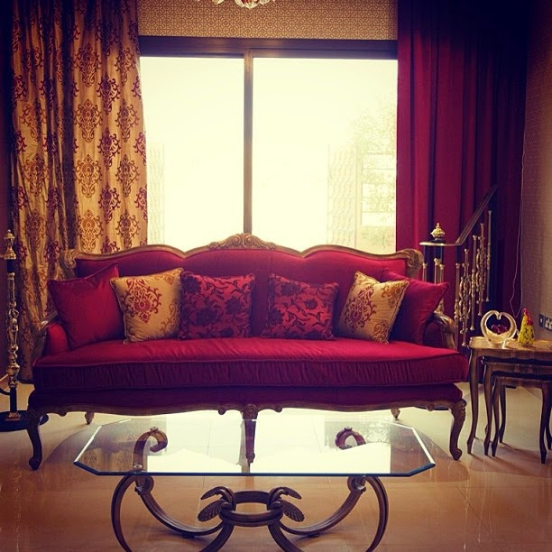 red vintage sofa by the window in a room with a small table
