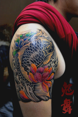 KOI fish tattoo design on the arm with a lotus flower