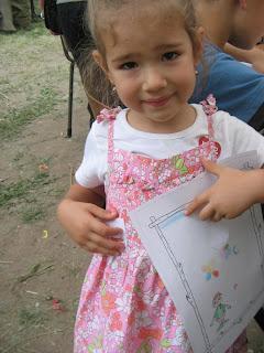 Virágos ruhás, copfos kislány félénken néz a kamerába, egyik kezével tartja rajzát Törpmanóról, a másikban meg magához szorítja a kapott lehúzósképet.