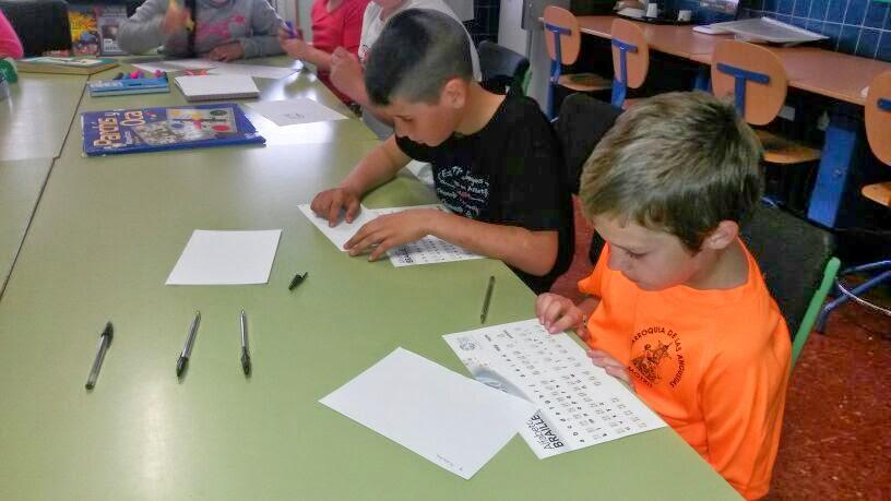 La imagen muestra a dos niños intentando leer en braille con el alfabeto delante