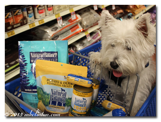 Westie in shopping cart with Natural Balance products