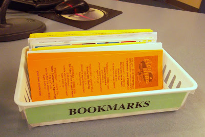 Collection of bookmarks on their sides, facing forward, in a basket labeled 'Bookmarks.' Bright orange bookmarks in the front of the stack proclaim that 'Every Hero Has a Story! Find Your Superpower at the Ashland Children's Library. Smaller typeface details events of the summer 2015 reading program.