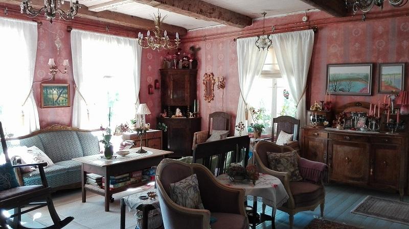 Koikkelan olohuoneen tunnelmaa luovat itse maalatut tapetit sekä kaikenlainen vanha ihana