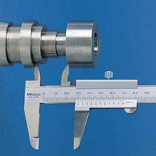 Vernier caliper used to measure inside diameters in industrial manufacturing.
