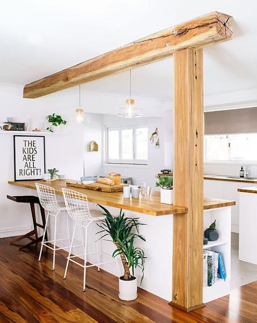 Cocina abierta con encimera de madera y muebles blancos
