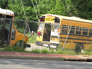 two yellow schools buses, one with front door open, other with rear door open