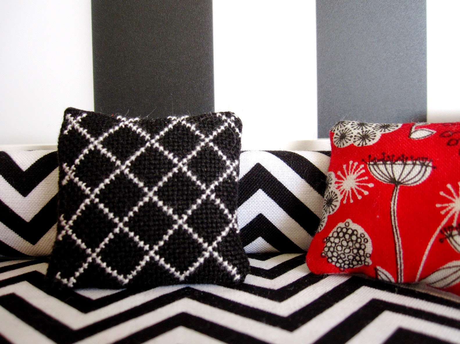 Modern miniature scene of a black and white lattice-embroidered cushion on a black and white chevron sofa against a wall with large black and white stripes. In the right corner is a red black and white mid-century modern flowered cushion.