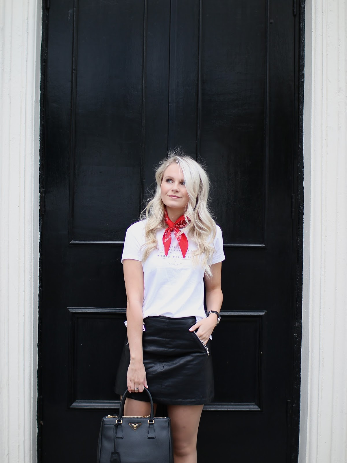 blonde women wearing leather mini skirt and graphic t shirt poses in front of London door