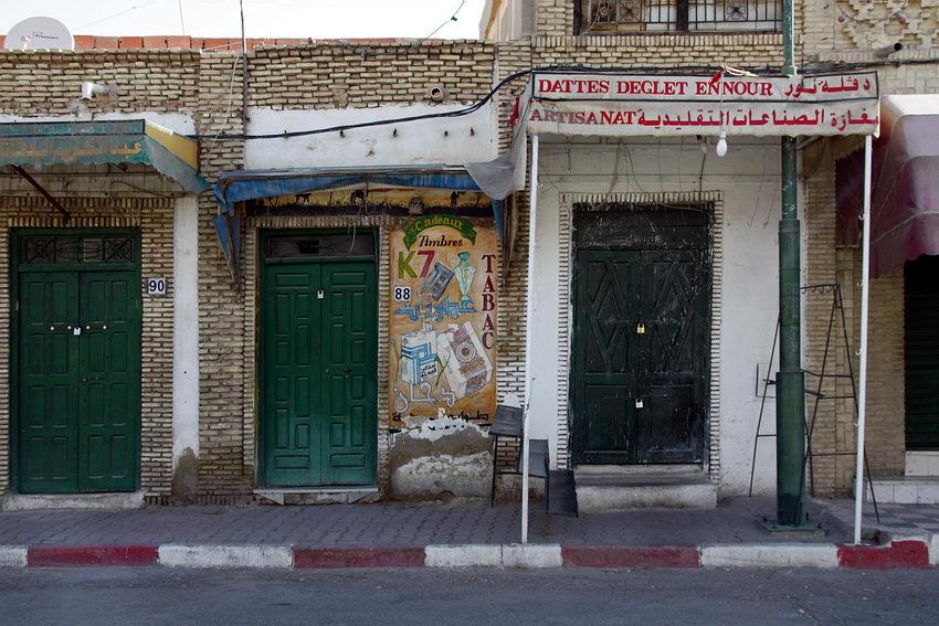 Pormenor de uma rua com estabelecimentos comerciais e pinturas na parede