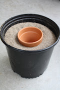 Push smaller clay pot down into the center of the bigger pot