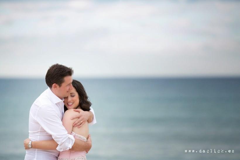 novios abrazados junto al mar en tonos pastel