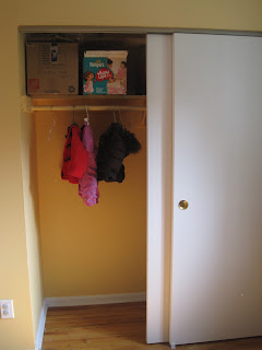 Open closet with just three items hanging, and two large boxes on the top shelf