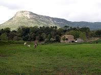 La masia de La Bauma i al seu darrere Sant Salvador des de la riera de Clarà