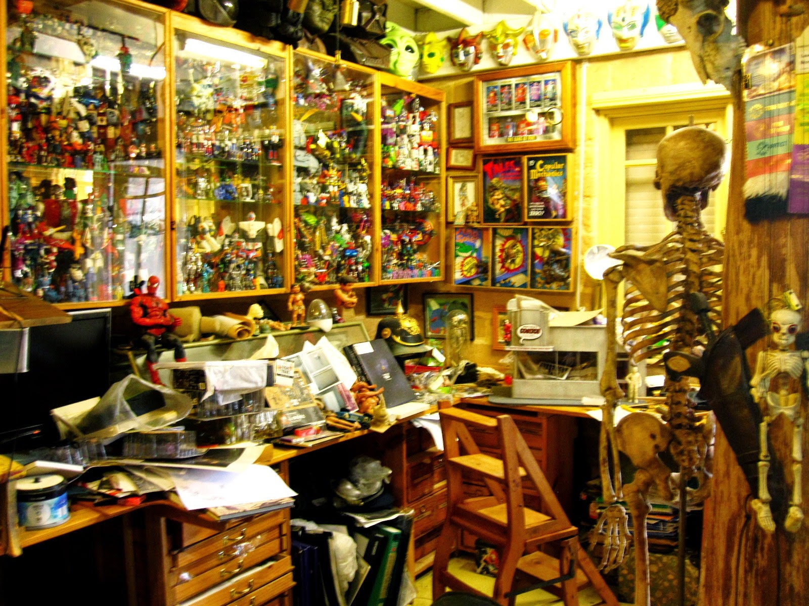 Workspace surrounded with glass cabinets full of Japanese toys.