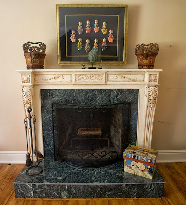 closer look to the fireplace reveal antique  pieces, marble materials and beautiful carved design