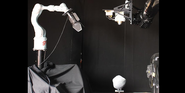 A real spacecraft camera mounted on a robot arm moving towards a model asteroid provided a practical test of image-based navigation software for ESA's Asteroid Impact Mission. A second robot arm plus camera, seen to the left, captured details of the descent. The testing took place at GMV in Madrid, Spain, during autumn 2015. Credit: ESA/GMV