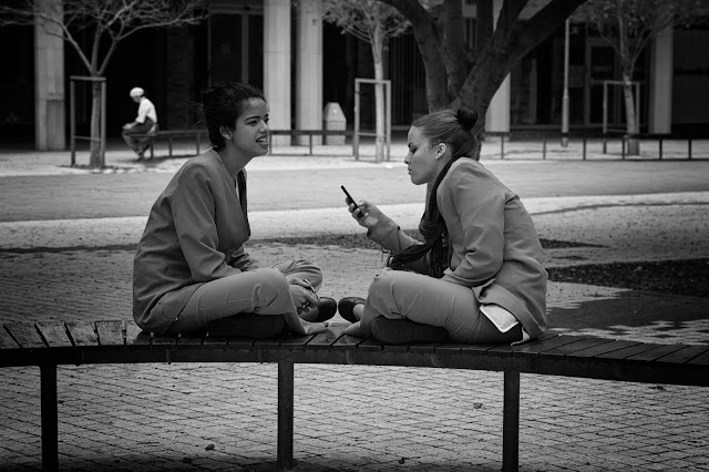 Two young women on a bench - a third in the distance