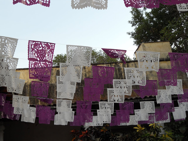 Purple and white papel picado banners over the cuexcomate
