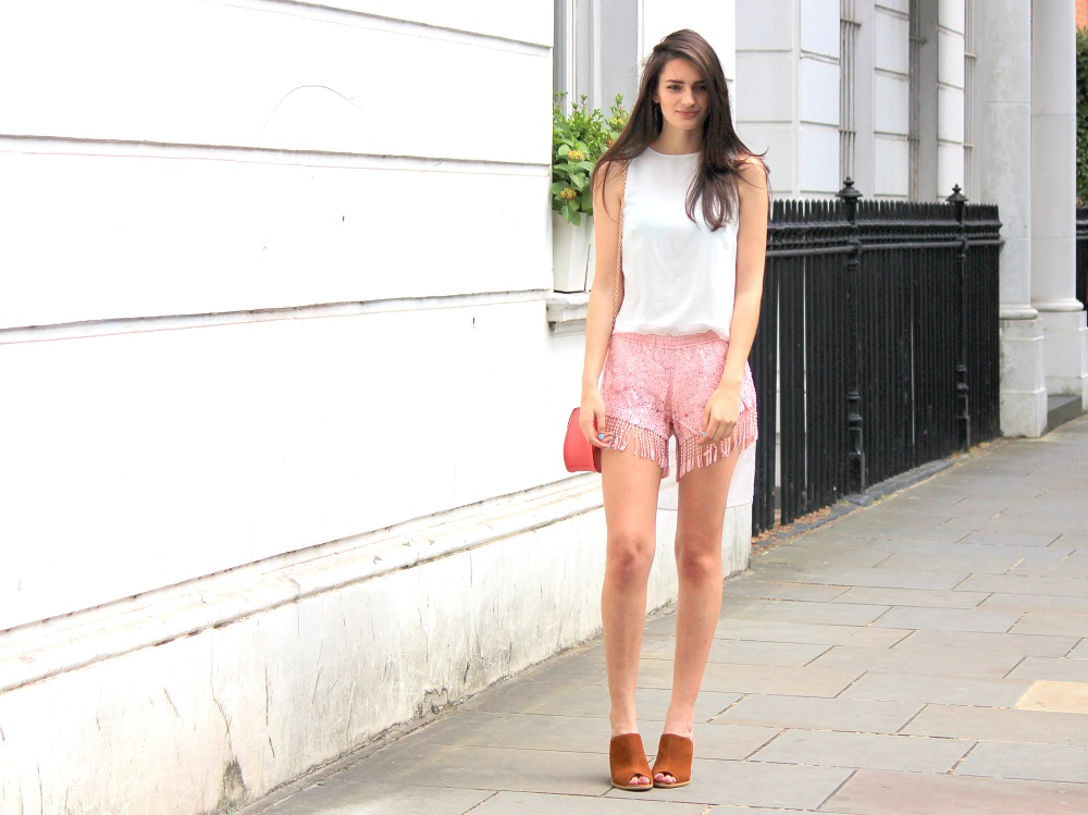 peexo fashion blogger wearing pink fringe shorts and mini bag and mules