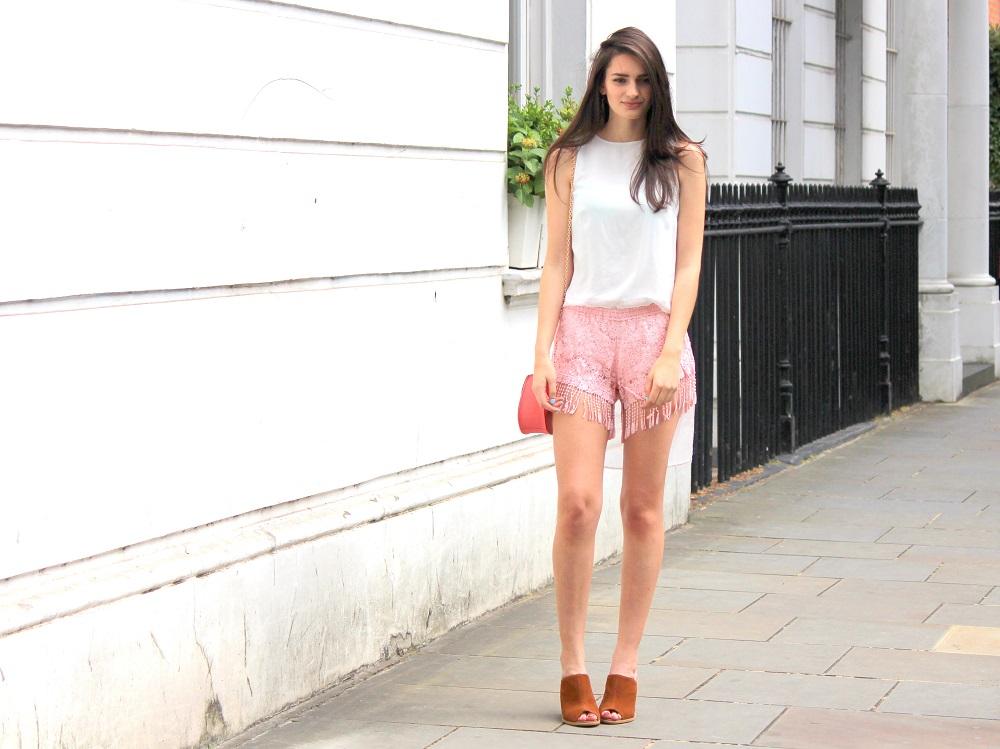 peexo fashion blogger wearing pink fringe shorts and mini bag and mules