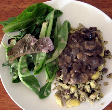 Thanksgiving leftover scramble with egg, mashed potato, olives, artichoke hearts, parsley, mushroom gravy, and a side salad