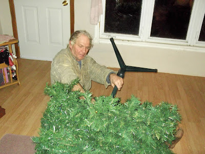 man adjusting xmas tree stand