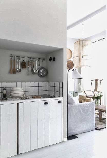 Small white kitchen in a French apartment with black grout and white paneled cabinet doors with black pulls