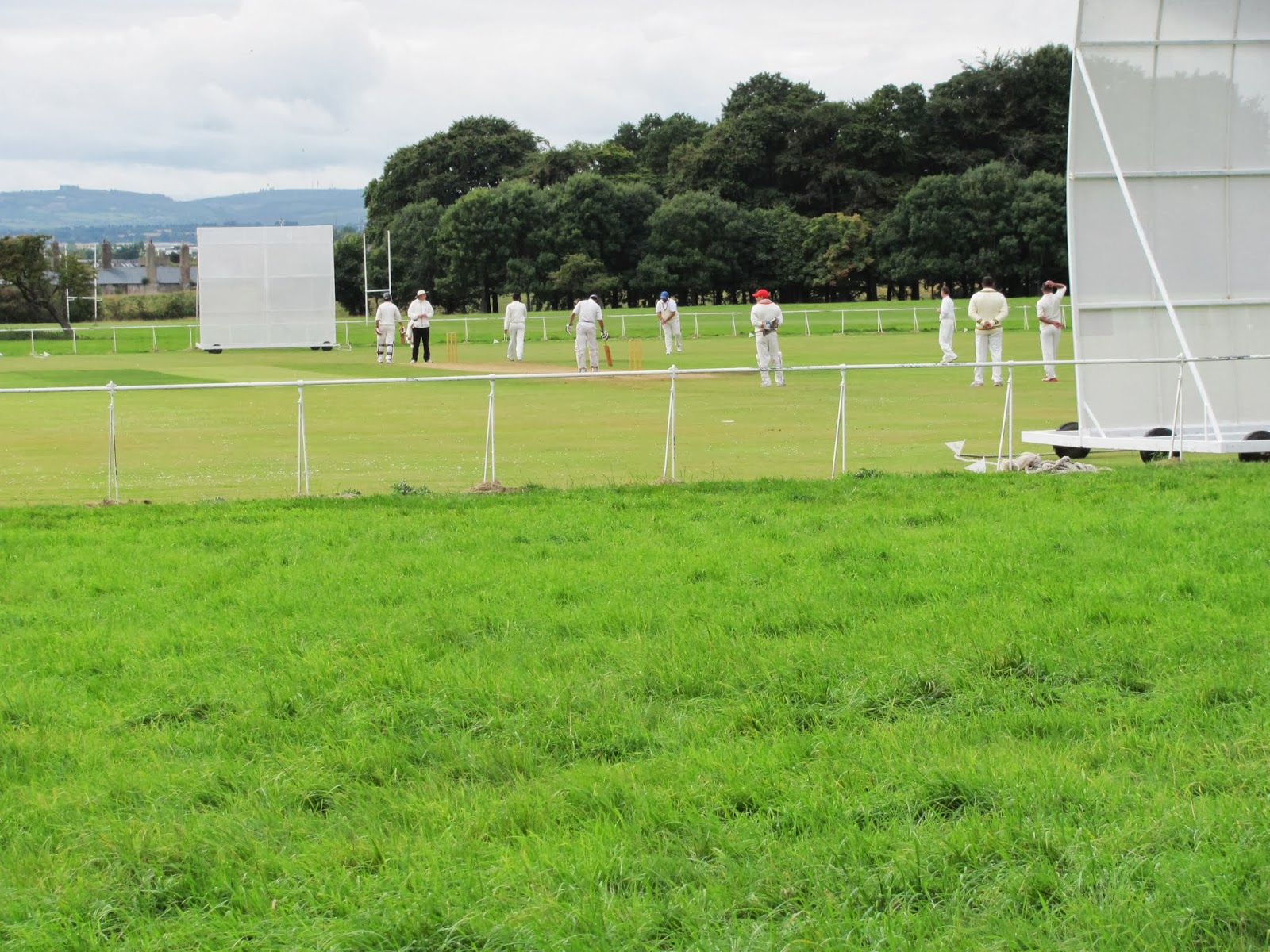 People dress in white and play cricket- bafflingly- at Phoenix Park in Dublin, Ireland