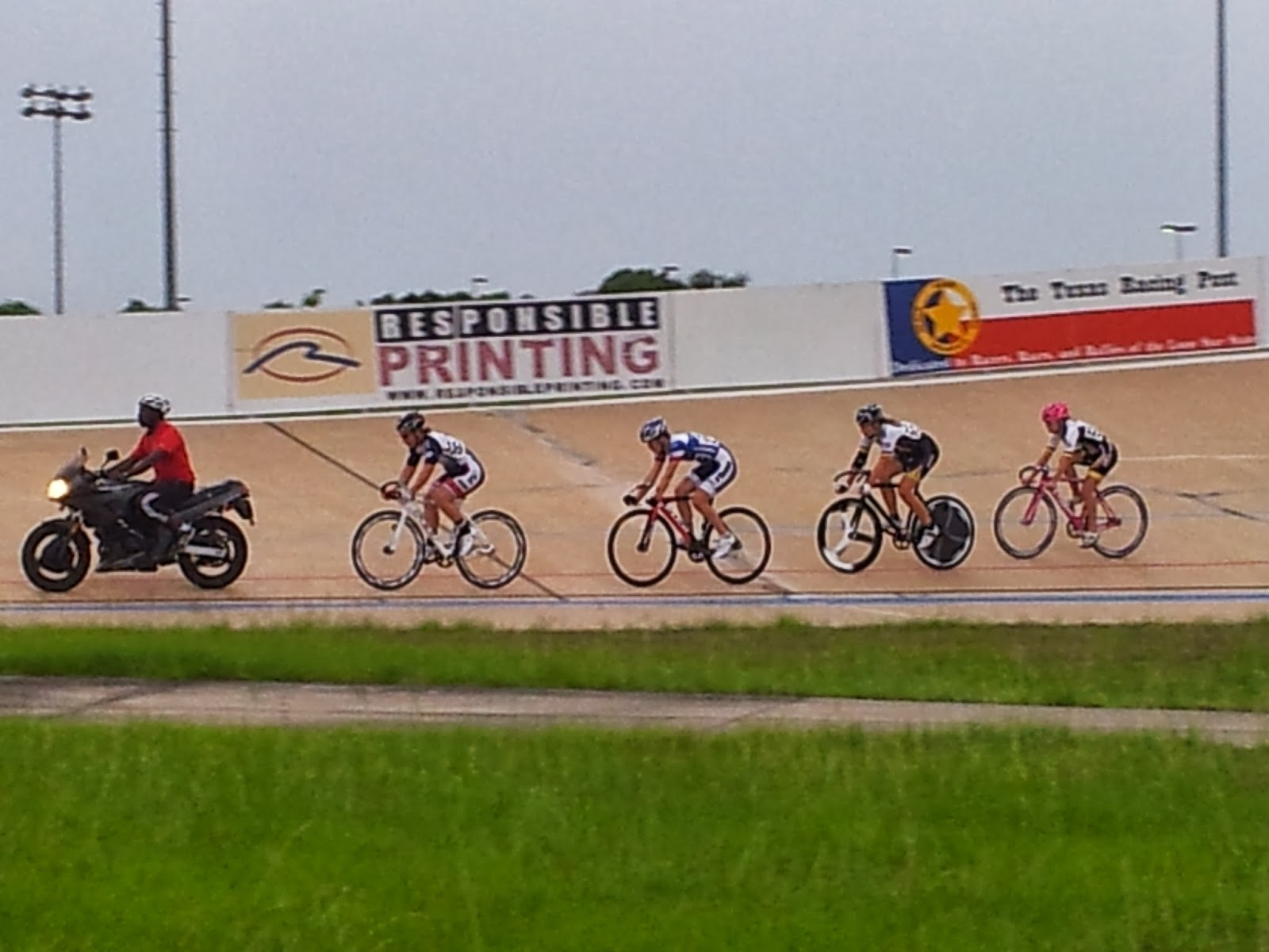 Cyclists being paced by motorcycle during race at Alkek Velodrome