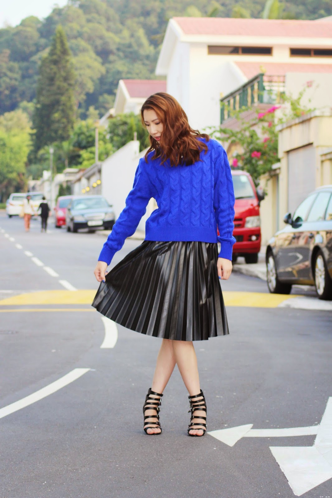 Styling blue sweater with black pleated faux leather midi skirt and strappy heeled sandals