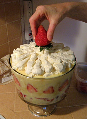 Hand Adding Whole Strawberry to Top of Trifle