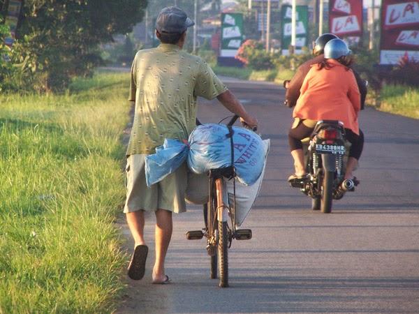 Seorang bapak sedang mengayunkan sepedanya