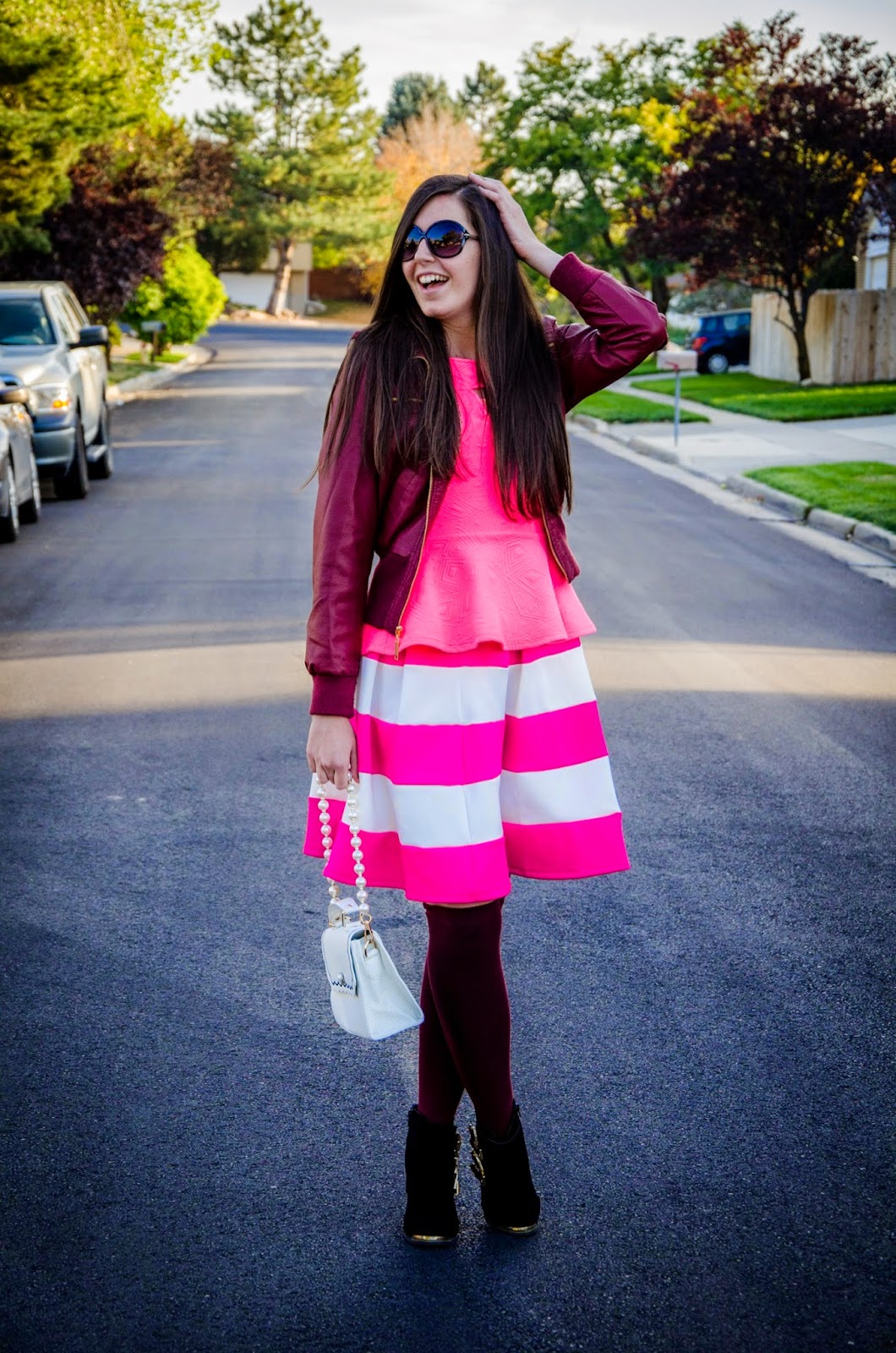 from summer to fall wear, summer to fall transitional outfit, how to wear a striped skirt in summer and fall, fall wear, burgundy leather jacket, pink striped skirt, pink peplum top, knee high socks, thigh high socks, wedges, ankle booties,