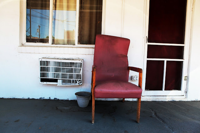 A beat up chair and window unit air conditioner outside of a shitty motel in Greeley, Colorado.
