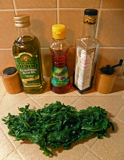 Cooked Kale with Bottles of Balsamic, Olive Oil, Salt, Pepper, and Hot Chili Oil