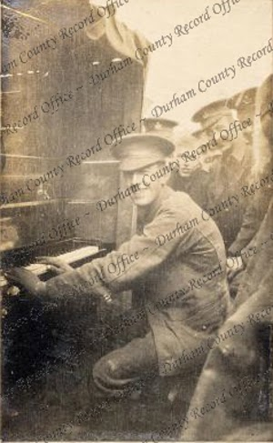 Soldier 'Barney' McArdle, 7th Battalion, Durham Light Infantry, playing the piano in a trench at Armentières, France, c.1915 (D/DLI 2/7/18(84))