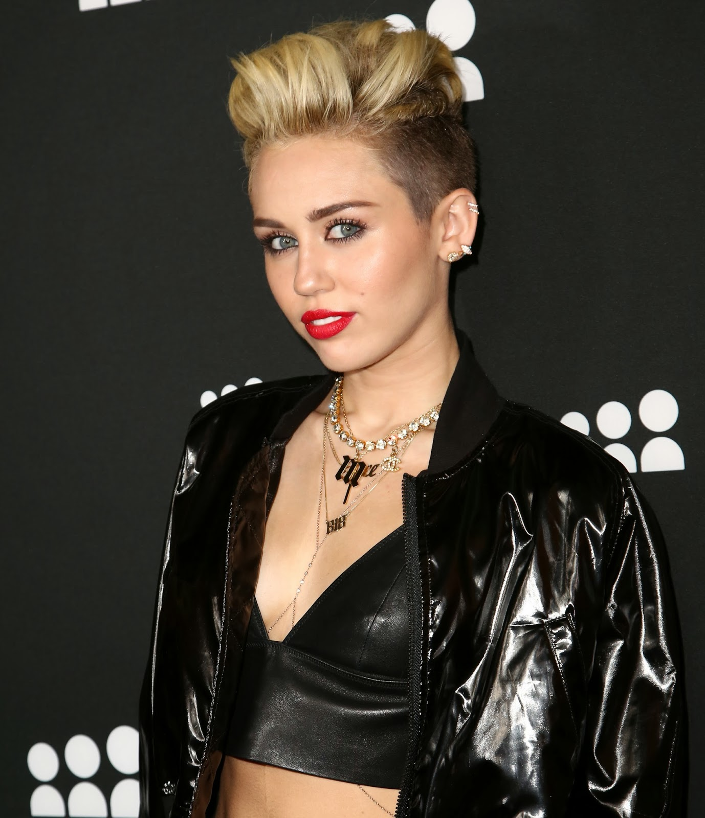 Miley Cyrus wearing an Initial Necklace and other personalized jewelry.