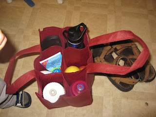 reusable wine bottle bag repurposed as beach bag with sunscreen, apples, water bottles and coffee mug