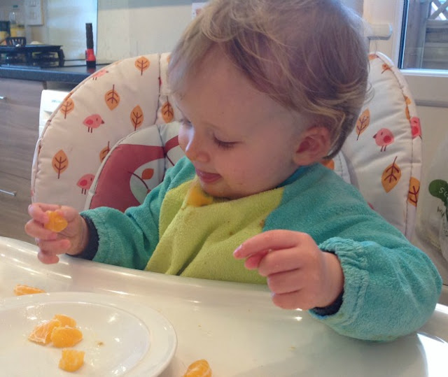 picture of a toddler spitting out orange pieces