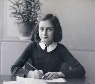 Anne Frank at a desk. Thirteen in 13 campaign