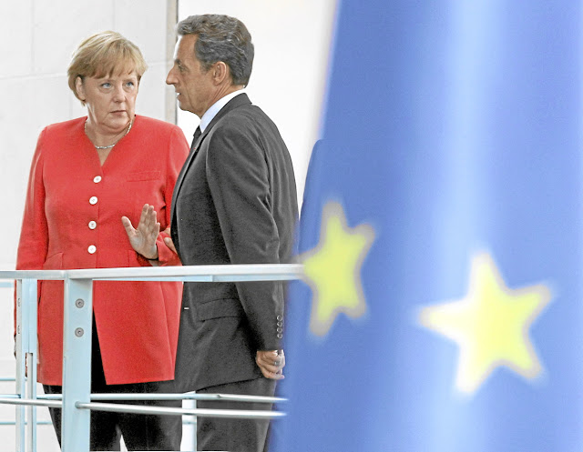 Merkel and Sarkozy, talking about the scoundrel Silvio Berlusconi?