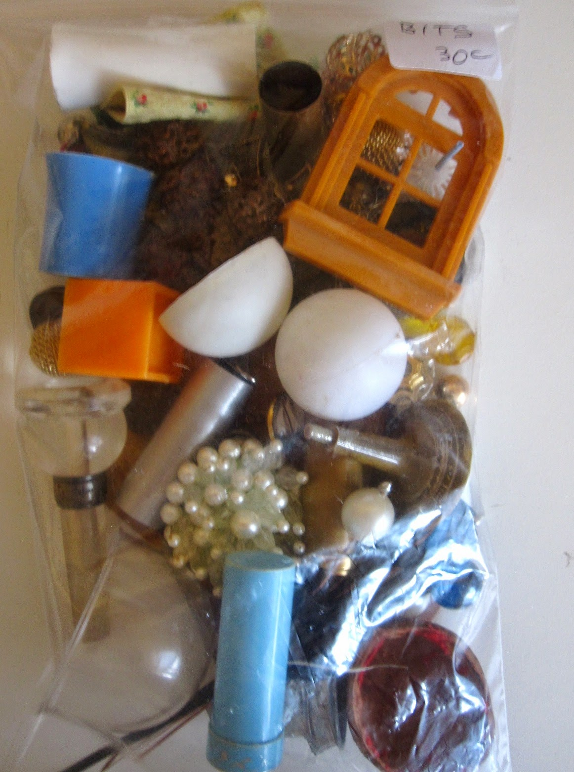 A5-sized bag of bits and bobs for miniature use. Bag is marked 'Bits 30c' and contains a variety of vintage earrings, containers and jewellery pieces.