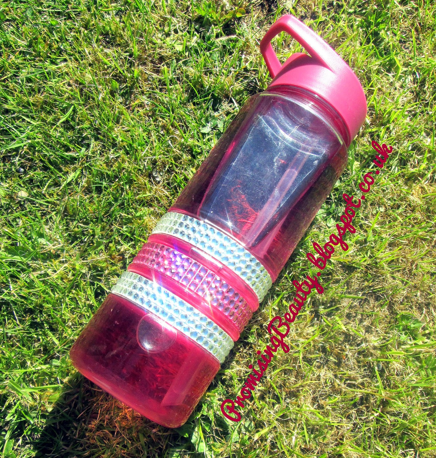 Water bottle with sparkly jewels, purple and pink. Filled with squash outside on the grass. 3 litres of water.