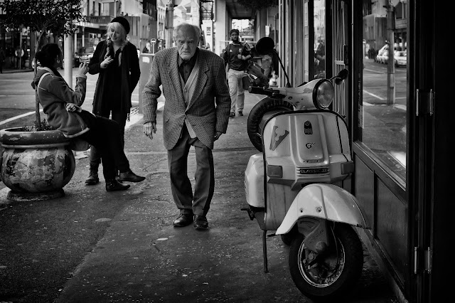 An elderly gentleman walks past two young girls who are smoking. A vesper scooter in the foreground