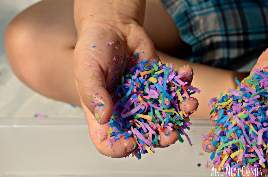 Close up of rainbow dyed shredded coconut sensory play from And Next Comes L