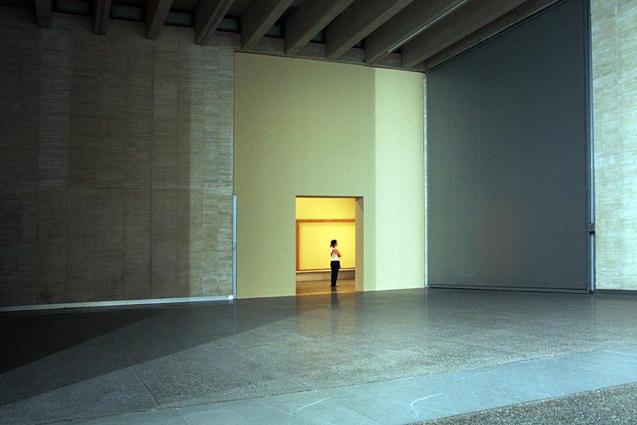 Vista sobre paredes vazias e apenas com uma abertura para outra sala, onde uma mulher está olhando ao longe. A luz da primeira sala resultou azulada e a da segunda ficou amarelada